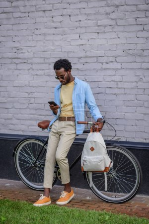Photo for Handsome african american man using smartphone while standing with bike near brick wall - Royalty Free Image