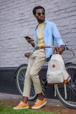 Photo for Stylish african american holding smartphone and looking away while standing with bicycle near wall - Royalty Free Image