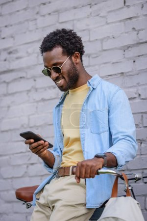 cheerful african american man smiling while standing near brick wall and using smartphone