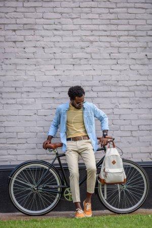 Foto de Guapo, elegante hombre afroamericano de pie con la bicicleta cerca de la pared de ladrillo - Imagen libre de derechos