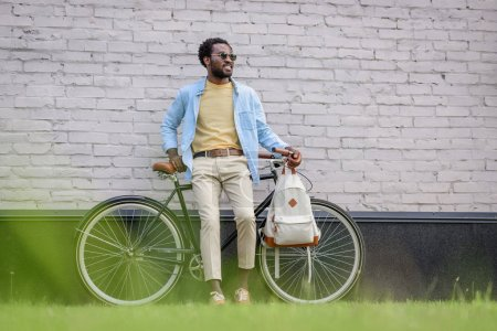 Photo for Stylish african american man looking away while standing with bicycle near brick wall - Royalty Free Image