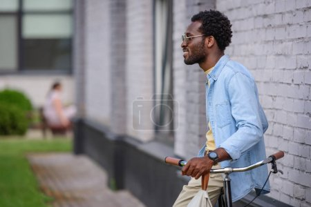 smiling african american man in sunglasses standing with bicycle near brick wall