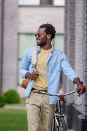 Photo for Stylish african american man in sunglasses looking away while standing with bicycle - Royalty Free Image