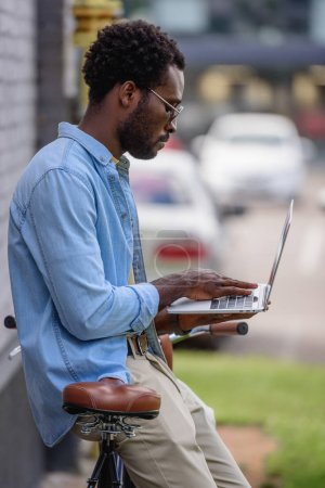 handsome african american man using laptop while standing near bicycle