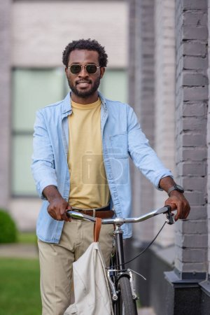 stylish african american man in sunglasses looking at camera while standing near bike