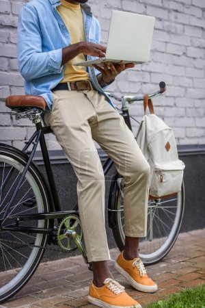 Photo for Partial view of african american man using laptop while standing near bike - Royalty Free Image