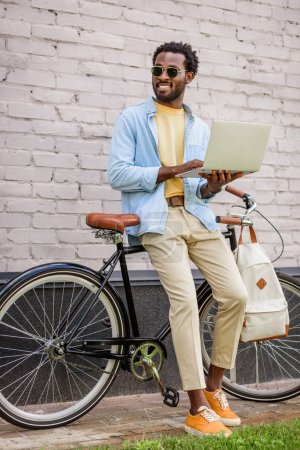 Photo for Cheerful african american man looking away while standing near bicycle and using smartphone - Royalty Free Image