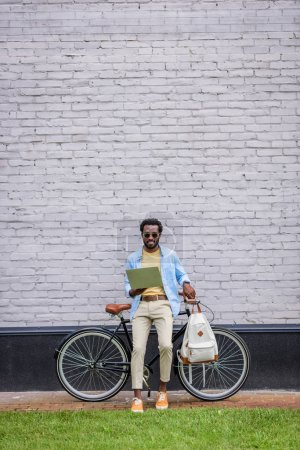 Photo for Stylish african american man standing by brick wall near bicycle and using smartphone - Royalty Free Image
