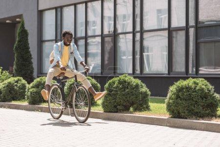 Photo pour Heureux, élégant homme afro-américain souriant tout en faisant du vélo - image libre de droit