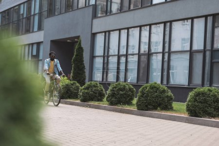 Photo pour Selective focus of african american man riding bicycle along building with glass facade - image libre de droit