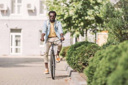 Photo pour Beau homme américain africain conduisant le vélo le long de la rue ensoleillée et des usines vertes - image libre de droit