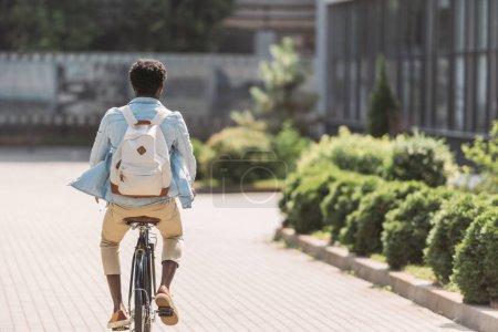 Photo pour Vue arrière de l'homme américain africain avec le vélo de sac à dos le long des buissons verts - image libre de droit