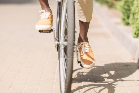 Photo for Cropped view of african american man riding bicycle along sunny street - Royalty Free Image