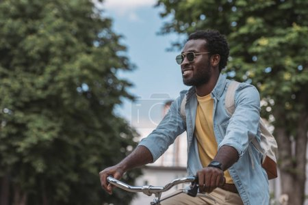 Photo pour Bel homme américain africain dans des lunettes de soleil regardant loin et souriant tout en conduisant le vélo - image libre de droit