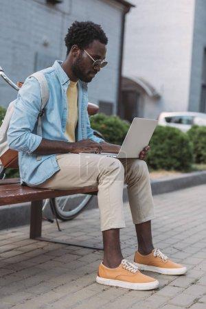 hombre afroamericano con estilo en gafas de sol usando el ordenador portátil mientras está sentado en el banco