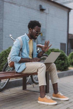homme afro-américain joyeux agitant la main tout en étant assis sur le banc lors d'un appel vidéo dans un ordinateur portable