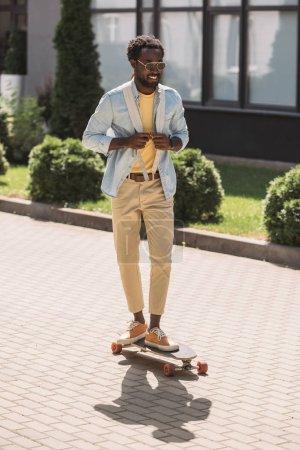 Photo pour Joyeux, élégant homme afro-américain souriant tandis que longboard sur la rue ensoleillée - image libre de droit