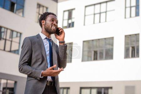Photo pour Homme afro-américain joyeux geste et détournement des yeux tout en parlant sur smartphone - image libre de droit
