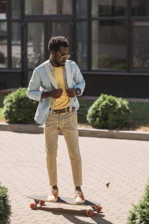 Photo pour Beau, élégant homme américain africain conduisant longboard sur la rue ensoleillée - image libre de droit