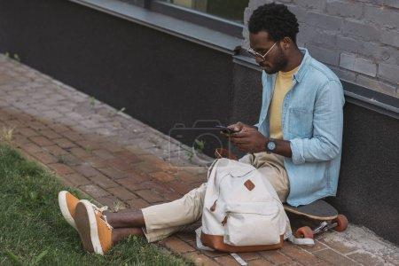 Photo pour Beau, élégant homme américain africain assis sur longboard et en utilisant smartphone - image libre de droit