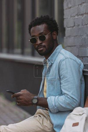 Photo pour Homme américain africain élégant dans des lunettes de soleil utilisant le smartphone et regardant l'appareil-photo - image libre de droit