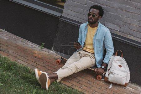 Photo pour Bel homme afro-américain élégant assis sur longboard et tenant smartphone - image libre de droit