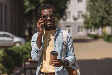 Photo pour Homme américain africain élégant dans des lunettes de soleil parlant sur le smartphone et retenant la tasse de papier - image libre de droit