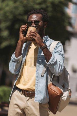 Photo pour Beau homme américain africain parlant sur le smartphone et buvant le café de tasse jetable - image libre de droit
