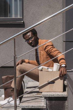 Photo for Sad, dismissed businessman sitting on stairs on street near carton box - Royalty Free Image