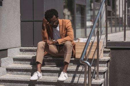 Photo pour Homme d'affaires américain africain bouleversé s'asseyant sur des escaliers près de la boîte de carton et retenant la main près de la tête - image libre de droit