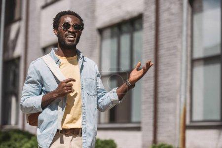 Photo pour Homme américain africain gai dans des lunettes de soleil souriant et faisant des gestes tout en regardant l'appareil-photo - image libre de droit