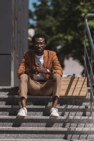 Photo for Upset, dismissed african american businessman sitting on stairs near cardboard box - Royalty Free Image