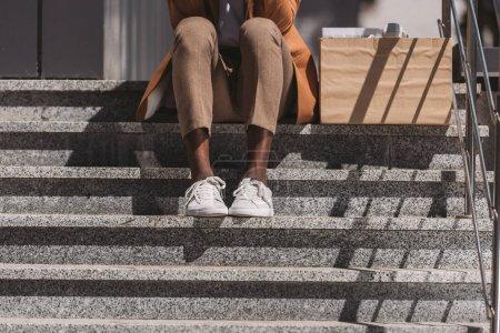 Photo pour Vue recadrée de l'homme d'affaires afro-américain congédié s'asseyant sur des escaliers près de la boîte de carton - image libre de droit