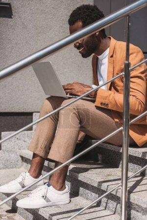 Photo pour Homme d'affaires américain africain de sourire s'asseyant sur des escaliers et travaillant sur l'ordinateur portatif - image libre de droit