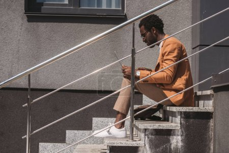 Photo for Side view of stylish african american businessman sitting on stairs and using laptop - Royalty Free Image