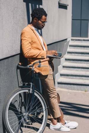 stylish african american businessman standing near bicycle and using laptop