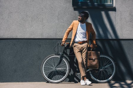 Photo pour Bel homme d'affaires afro-américain debout à côté du mur près du vélo et regardant loin - image libre de droit