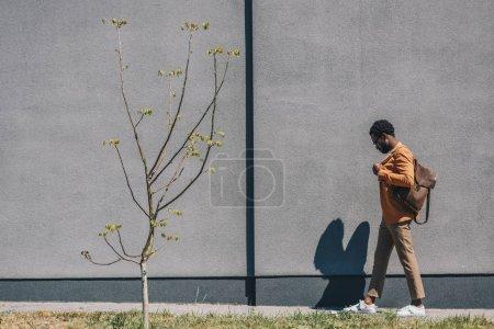 Photo pour Vue latérale de l'homme d'affaires afro-américain élégant marchant sur la rue ensoleillée le long du mur gris - image libre de droit