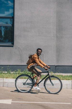 Foto de Alegre hombre de negocios afroamericano montando en bicicleta mientras sonríe a la cámara - Imagen libre de derechos