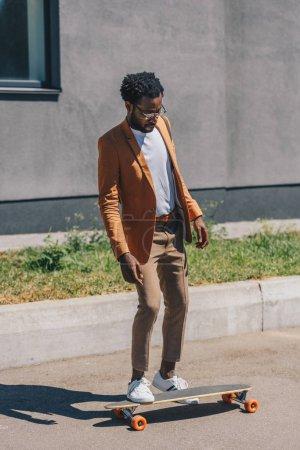 Photo pour Bel homme d'affaires américain africain dans des verres longboarding sur la rue d'été - image libre de droit