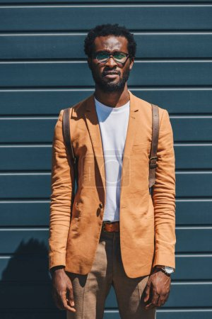 Photo for Handsome, stylish african american businessman in glasses looking at camera while standing near wall - Royalty Free Image
