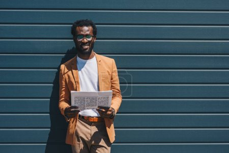 handsome african american businessman holding newspaper and looking at camera while standing by wall on street