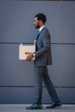 Photo for Side view of fired african american businessman holding carton box while walking on street - Royalty Free Image
