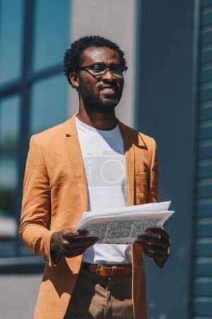 Photo pour Bel homme d'affaires afro-américain dans des lunettes tenant le journal et détournant les yeux - image libre de droit