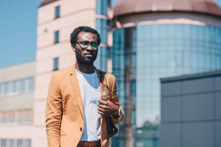 Photo pour Homme d'affaires américain africain pensif regardant loin avec des bâtiments sur le fond - image libre de droit