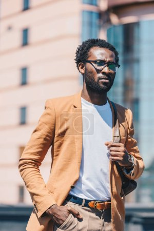 confident african american businessman holding hand in pocket and looking away