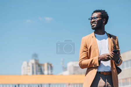 Photo for Cheerful african american businessman using smartphone and smiling with blue sky on background - Royalty Free Image