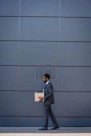 Photo pour Vue latérale d'un homme d'affaires afro-américain viré portant une boîte en carton tout en marchant le long du mur - image libre de droit