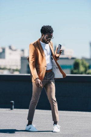 Photo for Cheerful, stylish african american businessman holding smartphone on rooftop - Royalty Free Image