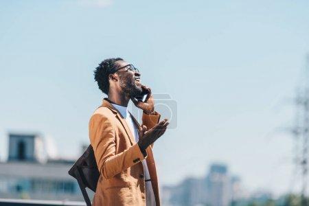 sonriente hombre de negocios afroamericano hablando en smartphone y haciendo gestos con el cielo azul en el fondo